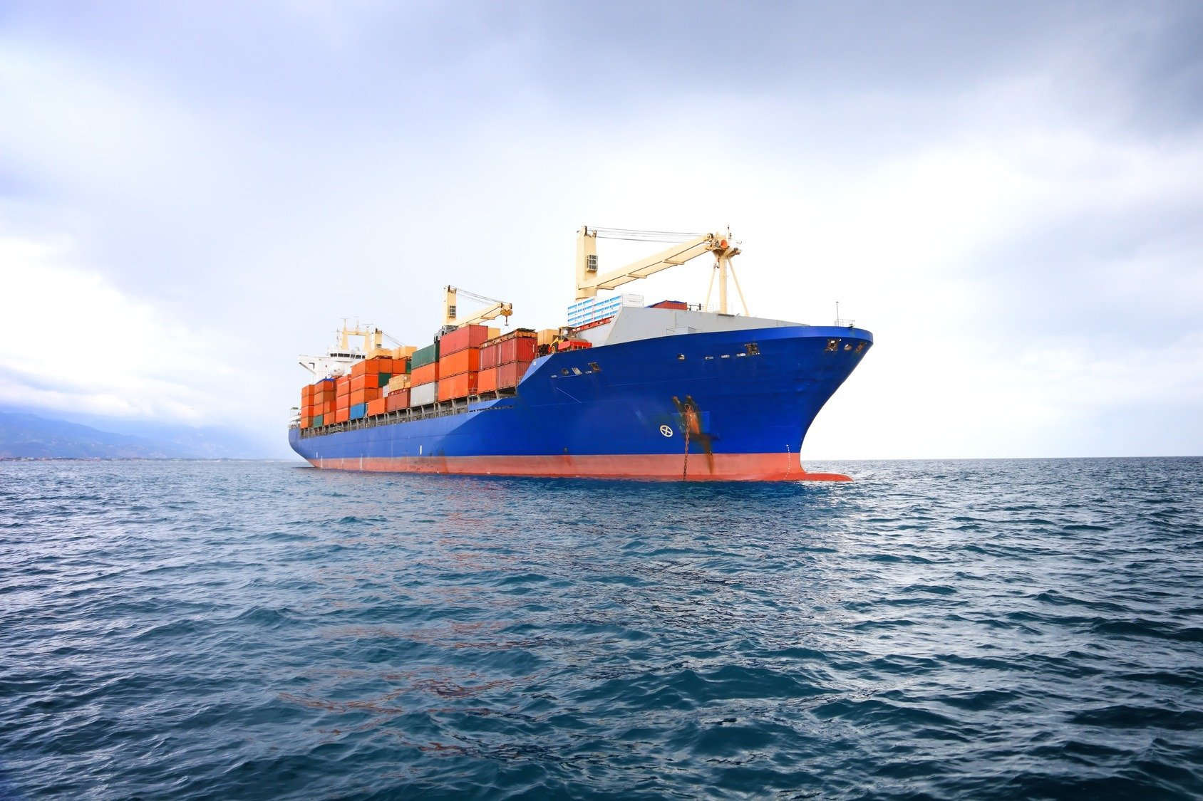 blue container ship at sea